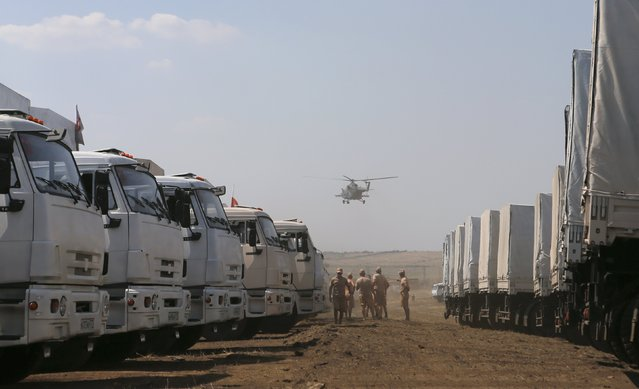 A military helicopter flies above a Russian convoy of trucks carrying humanitarian aid for Ukraine, parked at a camp near Kamensk-Shakhtinsky, Rostov Region, August 14, 2014. Artillery shells hit close to the centre of Ukraine's separatist-held city of Donetsk for the first time on Thursday, killing at least one person, as a large Russian aid convoy rumbled towards the border. (Photo by Maxim Shemetov/Reuters)