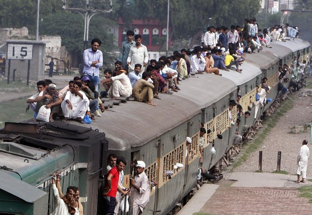 Pakistani passengers ride on crowded train returning from their hometown and villages after celebrating the Eid al-Fitr holiday to mark the end of the Muslim holy fasting month of Ramadan, to Lahore, Pakistan, Monday, July 11, 2016. (Photo by K.M.Chaudary/AP Photo)