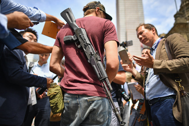 Journalists talk with a man openly carrying a gun in downtown on the first day of the Republican National Convention (RNC) on July 18, 2016 in Cleveland, Ohio. An estimated 50,000 people are expected in Cleveland, including hundreds of protesters and members of the media. The convention runs through July 21. (Photo by Jeff J. Mitchell/Getty Images)