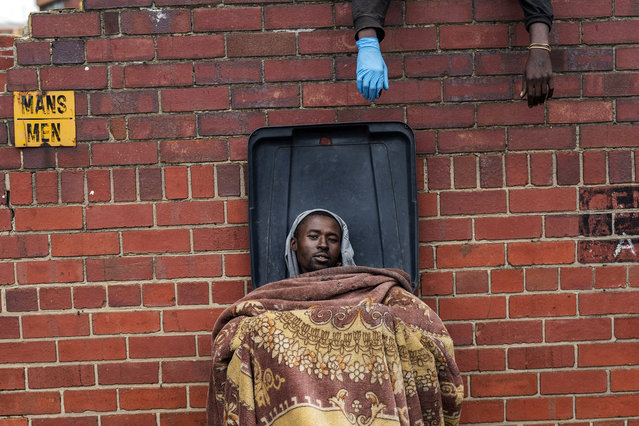 Henry sits in a bin as he and other homeless people rest at the Caledonian stadium downtown Pretoria, South Africa, Thursday April 2, 2020, after being rounded up by police in an effort to enforce a 21-day lockdown to control the spread of the coronavirus. Many of them being addicted, are receiving methadone syrup from a local NGO, and were complaining about the lack of sanitizer and soap. (Photo by Jerome Delay/AP Photo)