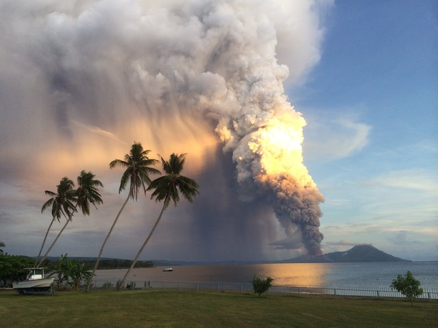 A photo taken on August 29, 2014, shows Mount Tavurvur erupting in eastern Papua New Guinea, spewing rocks and ash into the air, forcing the evacuation of local communities and international flights to be re-routed. Mount Tavurvur, which destroyed the town of Rabaul when it erupted simultaneously with nearby Mount Vulcan in 1994, rumbled to life early in the morning on the tip of the remote island of New Britain. (Photo by Oliver Bluett/AFP Photo)
