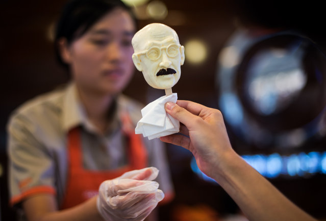 A woman sells an ice cream in the shape of executed Japanese war criminal Hideki Tojo at an ice cream store in Shanghai on September 2, 2015. An ice cream chain in China's commercial hub Shanghai is offering a lickable likeness of the head of executed Japanese war criminal Hideki Tojo to mark the 70th anniversary of the end of World War II. (Photo by Johannes Eisele/AFP Photo)