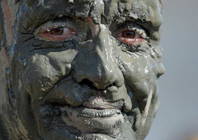 """A participant smiles after his handball match at the so called """"Wattoluempiade"""" (Mud Olympics) in Brunsbuettel at the North Sea, Germany July 30, 2016. (Photo by Fabian Bimmer/Reuters)"""