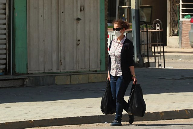 A masked woman walks past shops that are shuttered to help prevent the spread of the coronavirus during a curfew to help fight the spread of the coronavirus a nearly empty popular market in Baghdad, Iraq, Saturday, April 4, 2020. (Photo by Hadi Mizban/AP Photo)