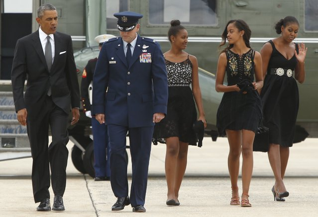 U.S. President Barack Obama (L-R) is escorted by U.S. Air Force Colonel John Millard as Obama, his daughters Sasha and Malia and first lady Michelle Obama arrive to board Air Force One at Joint Base Andrews, Maryland August 30, 2014. Obama is visiting New York on Saturday to attend a personal event. (Photo by Jonathan Ernst/Reuters)