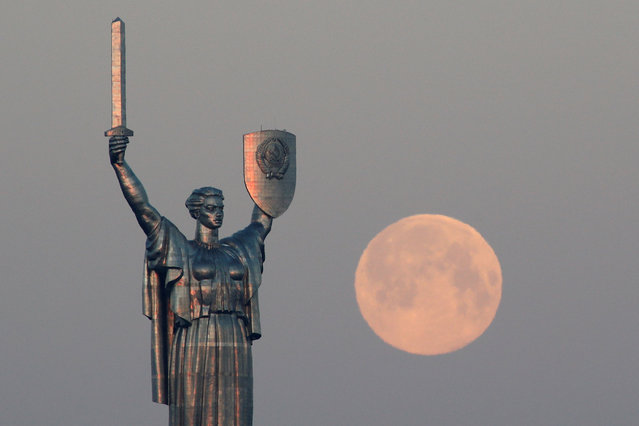 """The Pink Supermoon sets behind the giant """"Mother of the Motherland"""" monument in central Kiev, Ukraine on April 8, 2020. (Photo by Valentyn Ogirenko/Reuters)"""