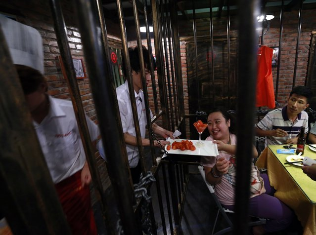 A customer receives a dish between iron bars as she eats a dinner at a jail-themed restaurant in the Chinese port city of Tianjin September 9, 2014. (Photo by Kim Kyung-Hoon/Reuters)