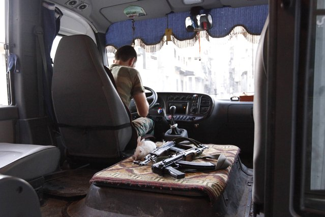 A rabbit is pictured next to weapons in a Free Syrian Army bus in Bustan Al-Basha district in Aleppo September 18, 2012. (Photo by Zain Karam/Reuters)
