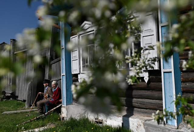 Elderly people, including veteran Pyotr Beznosenko, sit on a bench and receive congratulations during the celebrations of Victory Day, which marks the anniversary of the victory over Nazi Germany in World War Two, amid the outbreak of the coronavirus disease (COVID-19) in the town of Tara in Omsk Region, Russia on May 9, 2020. (Photo by Alexey Malgavko/Reuters)