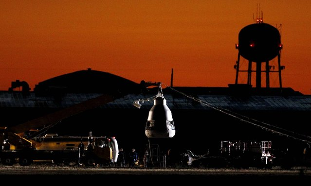 As the sun rises on Sunday, October 14, workers prepare at the launch site for the rescheduled mission. (Photo by Ross D. Franklin/Associated Press)