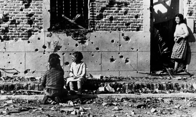 Children, unaware of the horror of war, play in front of the shrapnel-hit facade of No 10 Peironcely street, Madrid, Spain. November-December 1936. (Photo by Robert Capa/International Center of Photography/Magnum Photos)