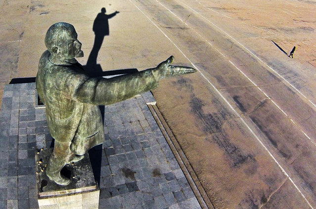 In this aerial file photo taken on Tuesday, October 31, 2017, a woman walks past a statue of Soviet Union founder Vladimir Lenin at the Russian leased Baikonur cosmodrome, in Kazakhstan. (Photo by Dmitri Lovetsky/AP Photo)