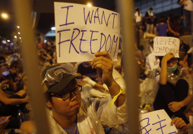 Protesters hold up signs during an evening rally attended by thousands in front of the government headquarters in Hong Kong September 27, 2014. (Photo by Bobby Yip/Reuters)