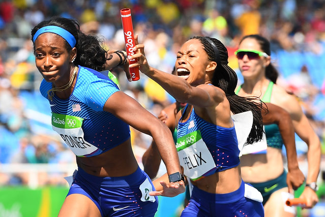USA's Allyson Felix hands the baton to USA's English Gardner competes in the Women's 4 x 100m Relay Round 1 during the athletics event at the Rio 2016 Olympic Games at the Olympic Stadium in Rio de Janeiro on August 18, 2016. (Photo by Franck Fife/AFP Photo)