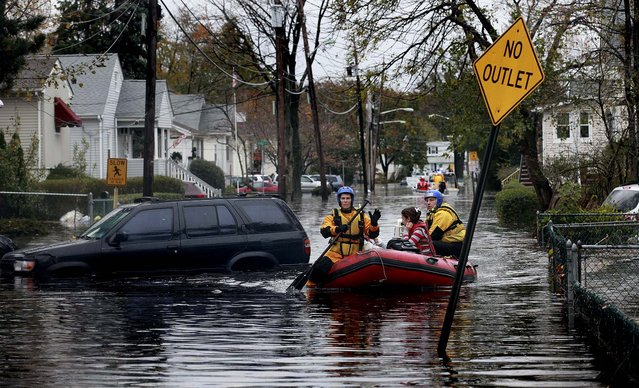 Residents are rescued from floodwaters after a levee broke in a neighboring town, in Little Ferry, N.J.  (Photo by Fred R. Conrad/The New York Times)