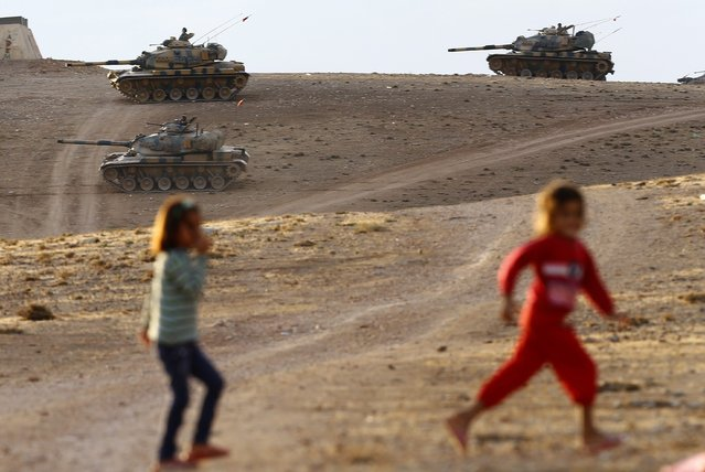 Turkish tanks guard the Syrian border after mortar shells hit Turkish territory in Suruc district, near Sanliurfa, Turkey 29 September 2014. Mortar shells from the ongoing battles between Kurdish forces and the advancing Islamic State extremist militia in northern Syria have landed in Turkey, broadcaster CNN Turk reported. At least one shell landed in the morning, following three the previous evening that injured three people in Suruc, a border town. (Photo by Sedat Suna/EPA)