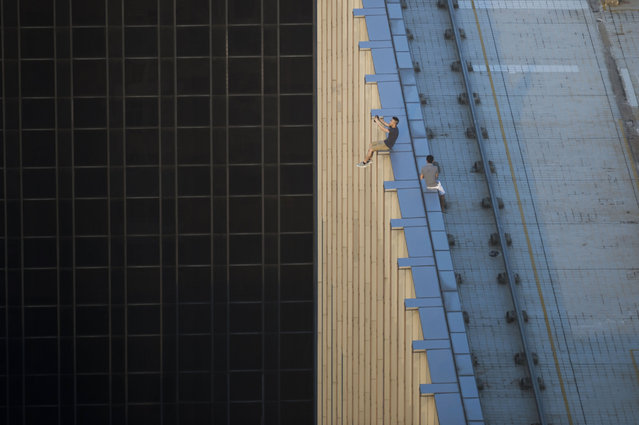 """In this photograph taken on August 23, 2016, two men take a series of selfies as they sit on the ledge of a high-rise building in an activity called """"rooftopping"""" in Hong Kong. (Photo by Romeo Gacad/AFP Photo)"""