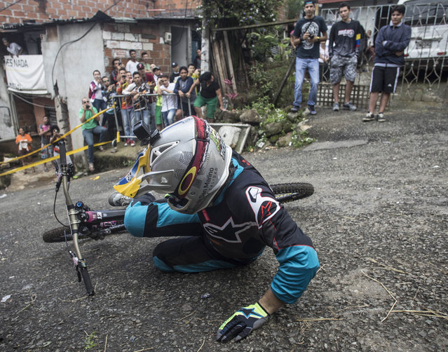 Residents look at a downhill rider during the Urban Bike Inder Medellin race final at the Comuna 1 shantytown in Medellin, Antioquia department, Colombia on November 19, 2017. (Photo by Joaquin Sarmiento/AFP Photo)