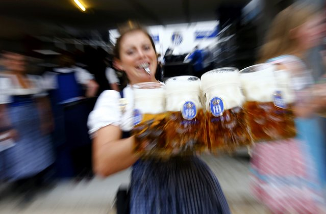 A waitress carries beer in a tent during the 182nd Oktoberfest in Munich, Germany, September 19, 2015. (Photo by Michael Dalder/Reuters)