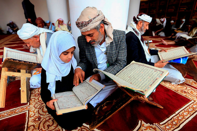 A Yemeni man reads with his daughter the Koran at the Great Mosque of Sanaa during the Muslim fasting month of Ramadan on April 26, 2020. (Photo by Mohammed Huwais/AFP Photo)