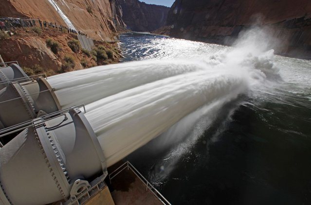 Water pours from river outlet tubes during an experimental high flow release from the Glen Canyon Dam in Page, Arizona, November 19, 2012. The total maximum release from the dam will reach approximately 42,300 cubic feet per second – 27,300 cfs of full-capacity powerplant releases and a bypass release through four river outlet tubes sending 15,000 cfs of water out over the Colorado River, according to an Interior Department statement. The release is part of a long-term protocol announced in May by Interior Secretary Ken Salazar to meet water and power needs and resolve problems with downstream sediment and non-native fish predation on the Colorado River below the dam. (Photo by Bob Strong/Reuters)