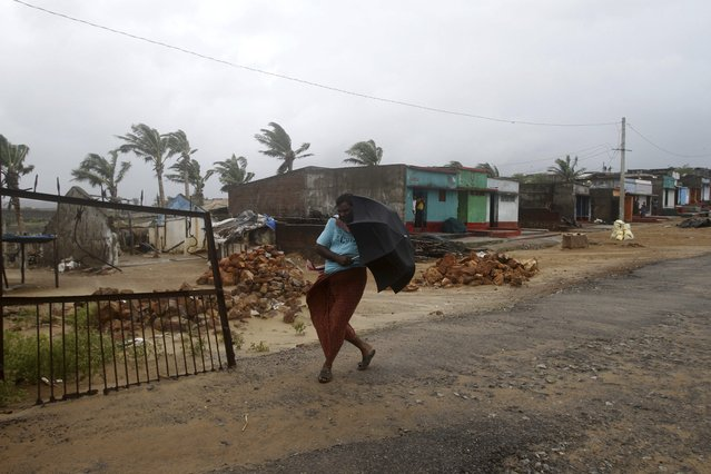 An Indian villager walks towards a shelter as heavy rain and wind gusts rip through the Bay of Bengal coast at Gopalpur, Orissa, about 285 kilometers (178 miles) north east of Visakhapatnam, India, Sunday, October 12, 2014. (Photo by Biswaranjan Rout/AP Photo)