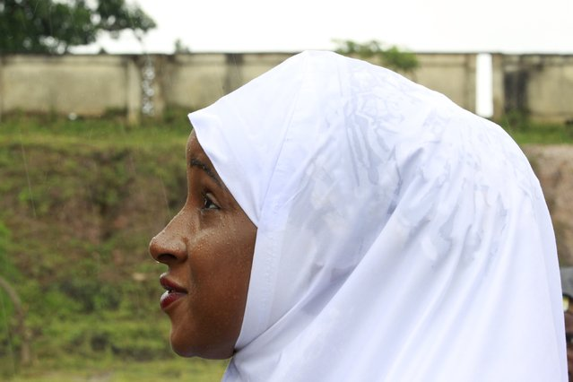 A Muslim woman looks on in the rain after prayers during the Muslim festival of Eid-al-Adha in Abuja, Nigeria September 24, 2015. (Photo by Afolabi Sotunde/Reuters)