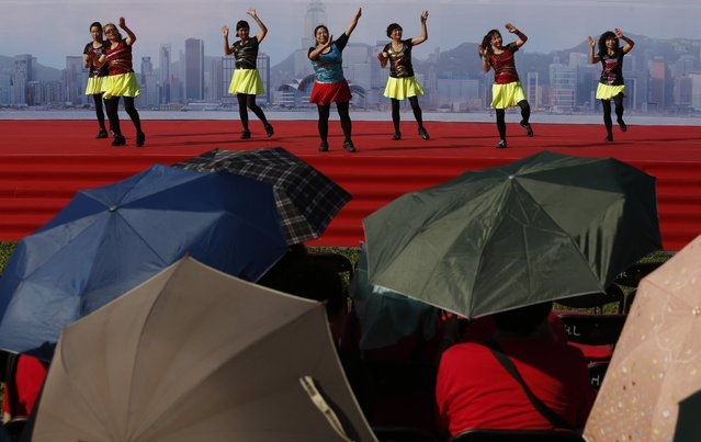 Performers dance at a pro-China event celebrating the upcoming Chinese National Day, held beside a student rally demanding true democracy, in Hong Kong September 26, 2014. Hundreds of children joined students demanding greater democracy for Hong Kong on Friday, capping a week-long campaign that has seen a large cut-out depicting the territory's leader as the devil paraded through the city and calls for him to resign. (Photo by Bobby Yip/Reuters)