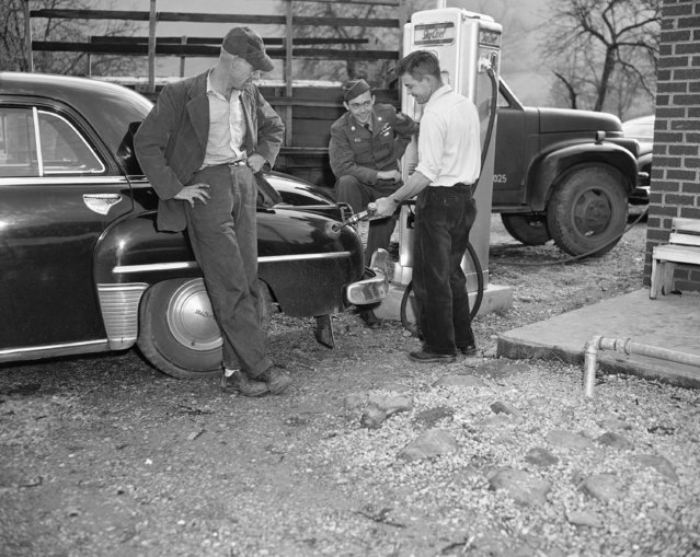 Cpl. Edward Dickenson, center, who accepted and then rejected Communism while a prisoner of war in Korea, fulfilled one of his prison camp dreams, November 23, 1953 in Cracker's Neck, Va., when he bought an automobile, one of the first things he did since getting home last night. Oscar Fraley fills up the tank as Dickenson's half-brother, Jim, looks on. Cpl. Dickenson got car from Jim, who was a prisoner of the Germans in World War II. (Photo by Gene Herrick/AP Photo)
