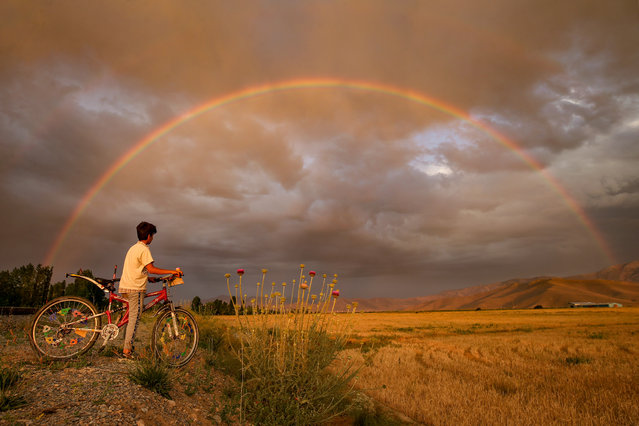 A boy with his bike is seen as rainbow appears after a rainfall in Edremit district of Van province in Turkey on July 08, 2020. (Photo by Ozkan Bilgin/Anadolu Agency via Getty Images)