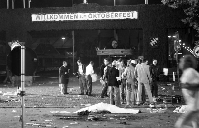 """In this September 26, 1980 file photo, with welcoming gate of the main entrance in rear a victim lies in front of a rescue team on the scene of a bombing blast at Munich's """"Oktoberfest"""" beer festival in Munich, Germany. German prosecutors said Wednesday that they have closed their investigation into a deadly far-right attack with thirteen people killed and more than 200 wounded on Munich's Oktoberfest in 1980, more than five years after they revived the probe in hopes that new testimony might point to previously unknown co-conspirators. The dead included the attacker, student Gundolf Koehler, a supporter of a banned far-right group. (Photo by Dieter Endlicher/AP Photo/File)"""