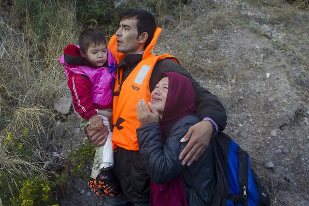 An Afghan refugee family embraces after arriving on an overcrowded dinghy in rough sea on the Greek island of Lesbos, after crossing a part of the Aegean Sea from the Turkish coast, October 2, 2015. (Photo by Dimitris Michalakis/Reuters)
