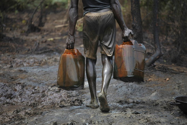 A man works at an illegal oil refinery site near river Nun in Nigeria's oil state of Bayelsa November 27, 2012. Thousands of people in Nigeria engage in a practice known locally as 'oil bunkering' - hacking into pipelines to steal crude then refining it or selling it abroad. The practice, which leaves oil spewing from pipelines for miles around, managed to lift around a fifth of Nigeria's two million barrel a day production last year according to the finance ministry. (Photo by Akintunde Akinleye/Reuters)