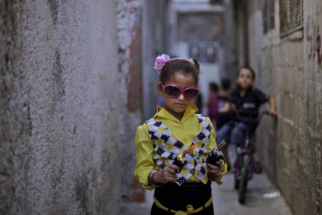 Palestinian Rama Abu alreesh, 6, displays two toy guns, while playing in an alley of Al-Ain refugee camp during the third day of Eid al-Fitr which marks the end of the Muslim fasting month of Ramadan near the West Bank city of Nablus, Sunday, September 12, 2010. Eid, one of the most important holidays in the Muslim world, is marked with prayers, family reunions and other festivities. (Photo by Muhammed Muheisen/AP Photo)