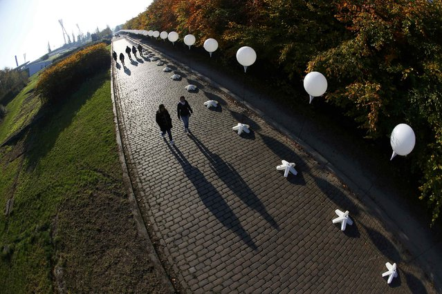 """People walk under stands with balloons placed along the former Berlin Wall location at Mauerpark, which will be used in the installation """"Lichtgrenze"""" (Border of Light) in Berlin November 7, 2014. (Photo by Pawel Kopczynski/Reuters)"""