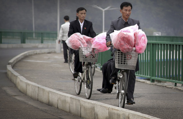 North Koreans carry decorative flowers to be used during upcoming anniversary celebrations on their bicycles, Thursday, October 8, 2015, in Pyongyang, North Korea. (Photo by Wong Maye-E/AP Photo)