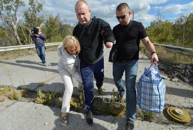Ukrainian prisoner of war Volodymyr Zhemchugov, who lost his arms and the use of his eyes in a 2015 mine blast in Ukraine's east during a conflict with pro-Russian separatists, is helped by Ukrainian First Deputy Speaker of the Verkhovna Rada Iryna Herashchenko to pass through a mine obstacle during a prisoners exchange in the town of Shchastya in Luhansk region, Ukraine, September 17, 2016. (Photo by Oleksandr Klymenko/Reuters)