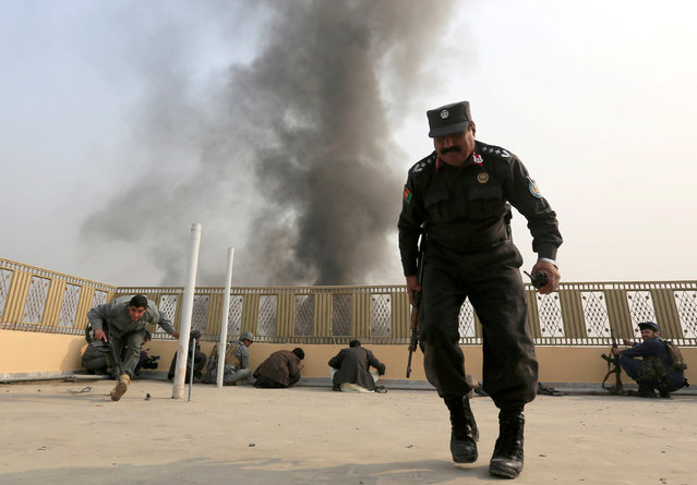 "Afghan police officers take position during a blast and gun fire in Jalalabad, Afghanistan January 24, 2018. Attahullah Khogyani, spokesman for the provincial governor said a group of gunmen stormed the office of the non-governmental organization, ""Save the Children"". (Photo by Reuters/Parwiz)"