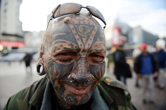 A tattooed man poses for pictures in Buenos Aires downtown on October 14, 2015. (Photo by Eitan Abramovich/AFP Photo)