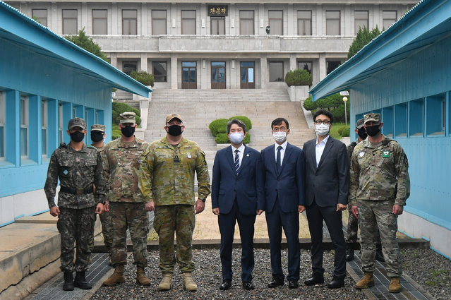 South Korean Unification Minister Lee In-young (C) and officials pose with U.S. and South Korean army soldiers at the military demarcation line during a visit to Panmunjom between South and North Korea in the demilitarized zone (DMZ) on September 16, 2020 in Panmunjom, South Korea. Unification Minister Lee In-young visit the truce village of Panmunjom for the first time since taking office, raising expectations he could send a message to North Korea amid stalled cross-border exchanges and cooperation. (Photo by Park Tae-hyun-Korea – Pool/Getty Images)