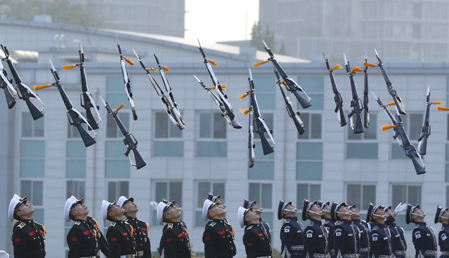Members of the South Korean honor guard throw their guns in the air during the honor guard ceremony for the Seoul International Aerospace and Defense Exhibition 2015, ADEX 2015, at the Defense Ministry in Seoul, South Korea, Tuesday, October 20, 2015. The event is held from Oct. 20 to Oct. 25 with many other affiliated events. (Photo by Lee Jin-man/AP Photo)