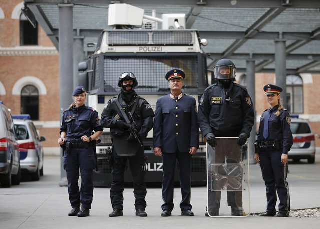 Austrian police officers pose in various uniforms in front of a water cannon at their headquarters in Vienna October 8, 2014. The uniforms include (L to R) light demonstration uniform, full combat adjustment for life threatening mission including gun (not used for riots in Austria), normal daily life uniform of commander, uniform of riot police officer, and normal uniform of police officer. (Photo by Leonhard Foeger/Reuters)