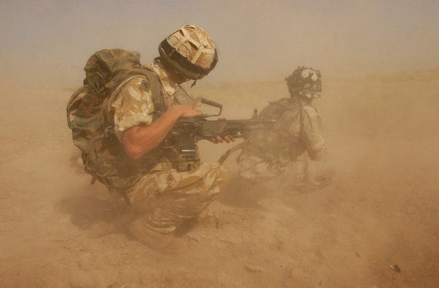 British Army soldiers, from the Royal Welch Fusiliers Regiment and Iraqi National Guards, take defensive positions on September 26, 2004 in Al Amarah, 180 km (112 mi) north of Basrah in southern Iraq, after having disembarked from a Chinox Helicopter during their first joint Eagle Airborne Vehicle Check Point Patrol. The capital of Maysan Province, Al Amarah, was a deprived area of Iraq under Saddam Hussein, as it was inhabited by both Shia Muslims and Marsh Arabs and resistant to any form of central control. (Photo by Marco Di Lauro/Getty Images)