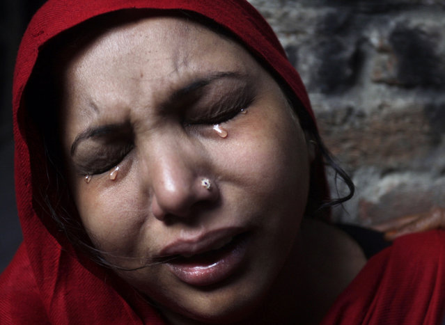 A Pakistani Christian woman weeps after visiting  her home which was damaged by an angry Muslim mob in Lahore, Pakistan, Sunday, March 10, 2013. Hundreds of Christians clashed with police in eastern and southern Pakistan on Sunday, a day after a Muslim mob burned dozens of homes owned by members of the minority religious group in retaliation for alleged insults against Islam's Prophet Muhammad. (Photo by K.M. Chaudary/AP Photo)