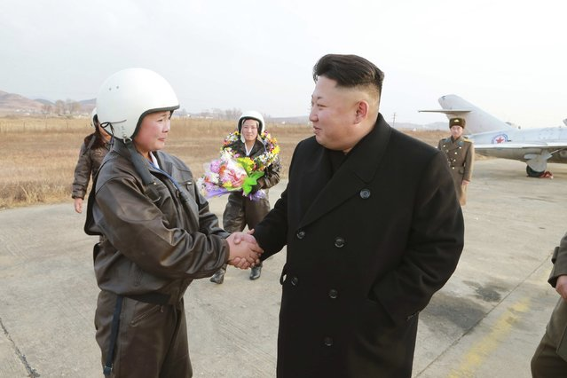North Korean leader Kim Jong Un shakes hands with a female pilot as he provides field guidance to the flight drill of female pilots of pursuit planes of the KPA Air and Anti-Air Force in this undated photo released by North Korea's Korean Central News Agency (KCNA) in Pyongyang November 28, 2014. (Photo by Reuters/KCNA)