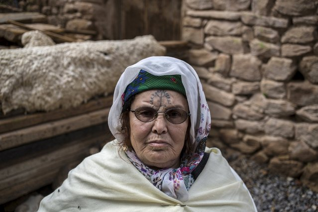 Khadra Kabssi, 74, a berber woman from the Chaouia region, who has facial tattoos, sits in her home in Chalma at the Aures Mountain near the eastern city of Batna, Algeria October 9, 2015. Among the Chaouia people of the Aures mountains, a woman's beauty used to be judged by her tattoos. (Photo by Zohra Bensemra/Reuters)