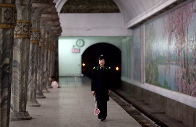 A conductor waits for a train at Puhung subway station in Pyongyang, on April 14, 2012. Pyongyang's metro network was opened between 1969 and 1972 by former President Kim Il Sung, and is supposedly the deepest in the world with its track some 110 meters underground. (Photo by Ed Jones/AFP Photo)