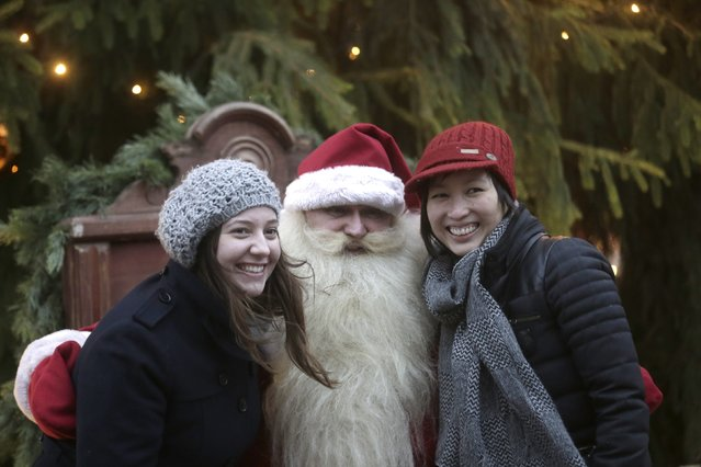 Two women pose for a picture with a man dressed as Santa Claus at the Christmas market in Riga December 6, 2014. (Photo by Ints Kalnins/Reuters)