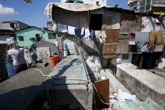 A woman takes a bath near their makeshift home inside the Manila South Public Cemetery in Pasay City, metro Manila October 30, 2015. (Photo by Romeo Ranoco/Reuters)