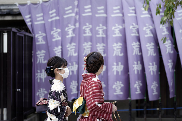 Kimono-clad visitors wearing protective masks to help curb the spread of the coronavirus walk at a shopping arcade at Asakusa district Thursday, October 22, 2020, in Tokyo. (Photo by Eugene Hoshiko/AP Photo)